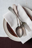 Vintage cutlery, different plates and brown tablecloth — Stock Photo