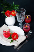 Table setting with red buttercups on a black background — Stock Photo