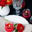 Table setting with red buttercups on a black background — Lizenzfreies Foto