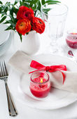 Table setting with red flowers — Stock Photo
