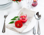 Table setting with red buttercup flowers — Stock Photo