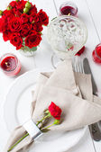 Festive table setting with red roses — Stock Photo