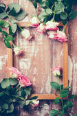 Roze rozen en een houten frame — Stockfoto