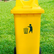 Yellow refuse bin in park — Stock Photo