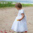 Baby girl looks and rose petals — Stock Photo #34851013