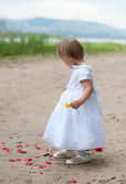 Baby girl looks and rose petals — Stock Photo