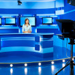 Stock Photo: Television newscaster at blue TV studio