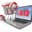 Stock Photo: Happy new year 2013. Laptop and gifts on shopping cart.