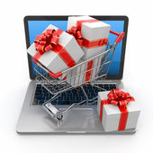E-commerce. Shopping cart and gifts on laptop — Stock Photo