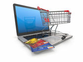 E-commerce. Shopping cart and credit cards on laptop — Stock Photo