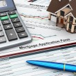 Mortgage application form with a calculator and house. - Stock Photo