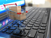 E-commerce. Shopping cart with cardboard boxes on laptop. — Foto Stock