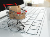 E-commerce. Shopping cart with cardboard boxes on laptop. — Stock Photo
