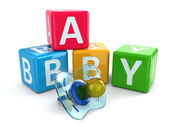 Dummy or pacifier and buzzword blocks with word baby. — Stock Photo
