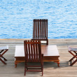 Stock Photo: Wooden arewith chairs and table on water