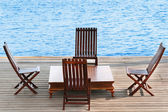 Wooden area with chairs and table on water — Stock Photo