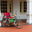 Empty bicycle rickshaw near classical colonial building — Stock Photo