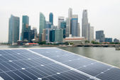 Solar panel and modern city — Stock Photo