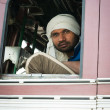 Indian driver in white turban in the cabin of his truck — Stock Photo