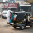 Stockfoto: Overloaded indituk tuk on typical messy street, India