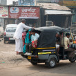 图库照片: Overloaded indituk tuk on typical messy street, India