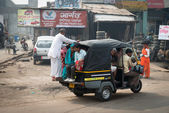 Overloaded indian tuk tuk on typical messy street, India — Stock Photo
