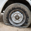 Deflated damaged tyre — Stock Photo