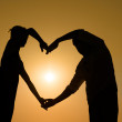 Sillhouette loving couple at sunset with heart — Stock Photo #18706761