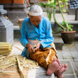 Balinese old women make baskets for offerings - Stock Photo