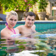 Happy young couple relaxing in a swimming pool — Stock Photo