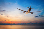 Airplane flying at sunset — Foto Stock