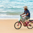 Stock Photo: Old native local man bicycling along a beach, Thailand
