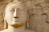 Buddha face on yellow stone — Stock Photo