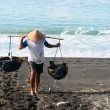 Traditional sea salt production on the volcanic black sand, Bali - Stock Photo
