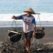 Traditional sea salt production on the volcanic black sand, Bali — Stock Photo