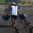 Traditional sea salt production on on the volcanic black sand, B - Stock Photo
