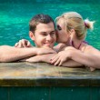 Kissing and relaxing in a swimming pool — Stock Photo