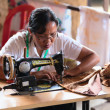 Balinese female tailor sew on a machine — Stock Photo