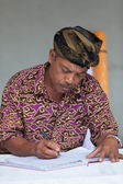 Balinese man maintain records in register book — Stok fotoğraf