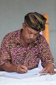 Balinesiska man underhåll poster i registret bok — Stockfoto