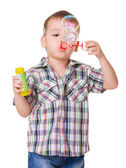 Boy blowing soap bubbles on white — Stock Photo