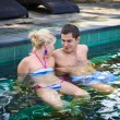 Happy smiling couple in swimming pool — Stock Photo