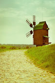 Vintage wooden windmill on stone road — Stock Photo