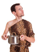 Looking up wild man with cooked food in a pan — Stock Photo