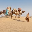 Постер, плакат: Caravan with bedouins and camels in desert