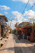 Tourist street decorated by traditional penjor on Bali — Stock Photo