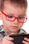 Clever kid is playing with smart cell phone — Stock Photo