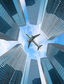 White airplane fly above modern city — Stock Photo