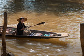 Floating asian vendors on long wooden boat — Stock Photo