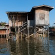 Traditional stilts house in water under blue sky — Stock Photo
